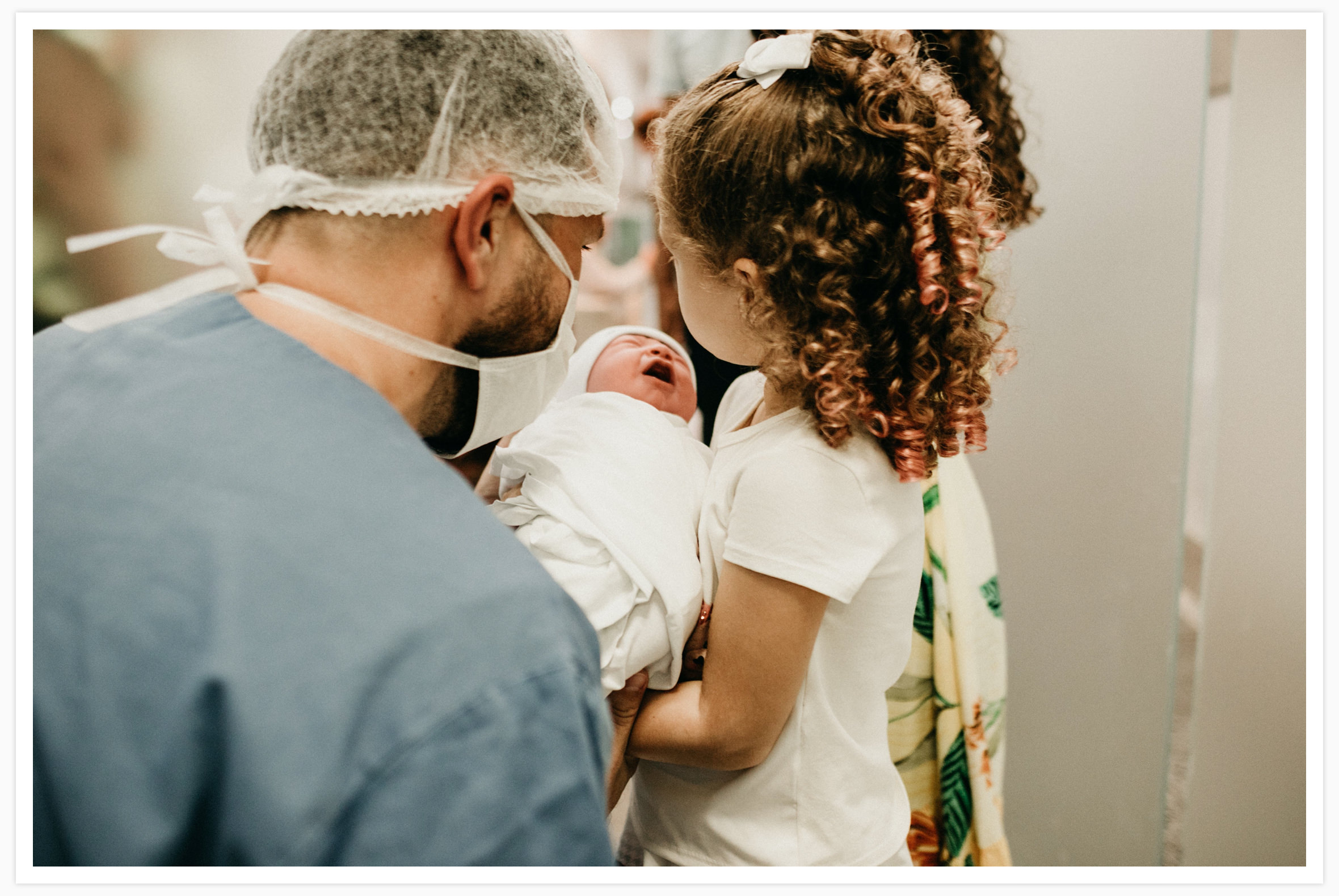 Dad and sister meet the new baby for the first time